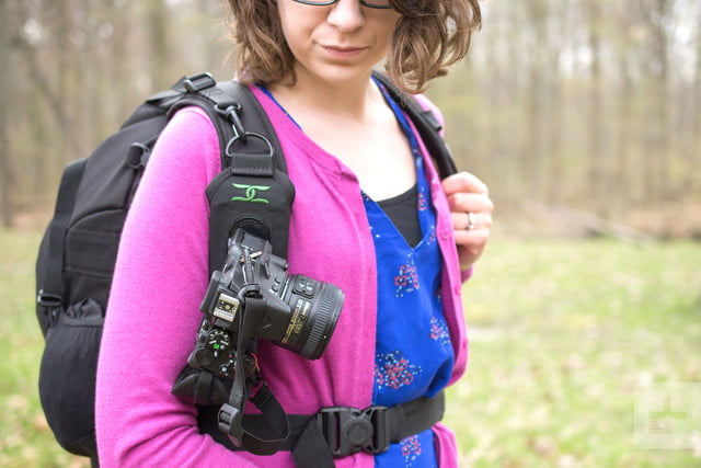 From the front and at an angle, the Cotton Carrier StrapShot holds a camera in place on a woman