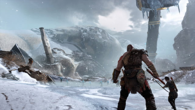 God of War Review | Kratos and Atreus looking down a snowy mountain pass with a dead titan forming the ridgeline
